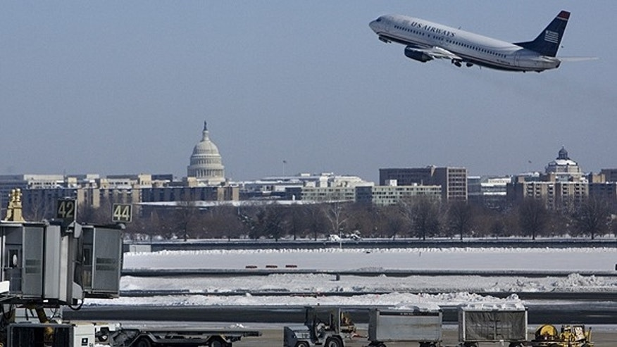 In this Feb. 8, 2010 file photo, with the U.S. Capitol in the background, a US Airways plane takes off from Washington's Reagan National Airport.