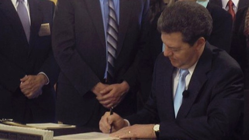 Kansas Gov. Sam Brownback signs an abortion restriction bill April 12 at the Statehouse in Topeka.