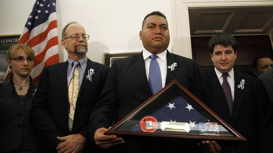 January 25: Daniel Hernandez, the intern credited with saving the life of U.S. Congresswoman Gabrielle Giffords after she was shot in Arizona, holds a U.S. flag presented to him by first responders from the September 11, 2001 attack on New York's World Trade Center