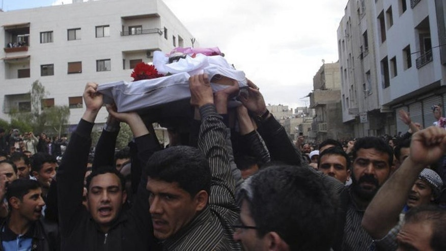 AP/citizen journalism image/Protesters carry the coffin of an activist who was killed
