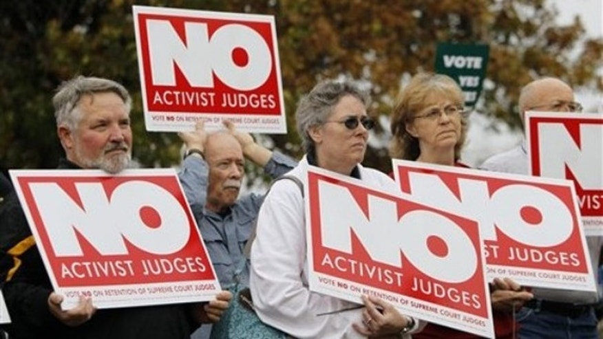 In this Oct. 25, 2010 file photo, demonstrators hold signs during a rally in support of a campaign to remove three state Supreme Court justices who joined in a unanimous ruling legalizing gay marriage in Des Moines, Iowa.