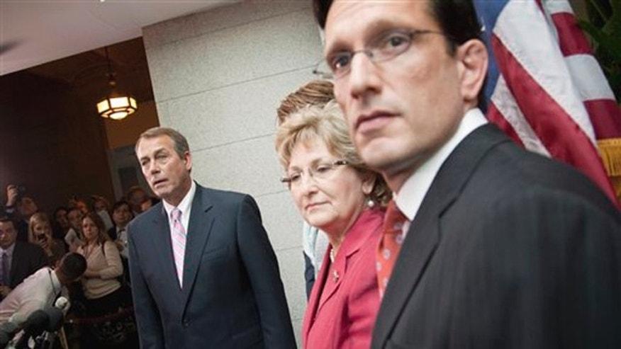 House Speaker John Boehner, left, listens to a question during a news conference on Capitol Hill April 15, 2011. From left are, Boehner, Rep. Diane Black, and House Majority Leader Eric Cantor.