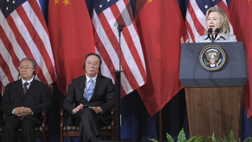 Secretary of State Hillary Rodham Clinton speaks as Chinese Vice Premier Wang Qishan, center, and Chinese State Counselor Dai Bingguo, left, listen during the opening session of the joint meeting of the U.S.-China Strategic and Economic Dialogue (S&ED), Monday, May 9, 2011, at the Interior Department in Washington. (AP Photo/Susan Walsh)