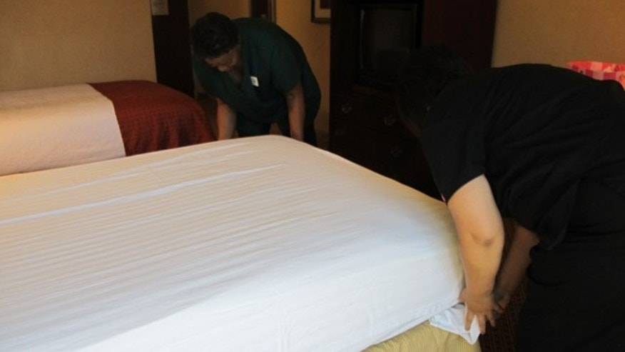 Housekeepers make a bed at the Holiday Inn Fresno Airport.