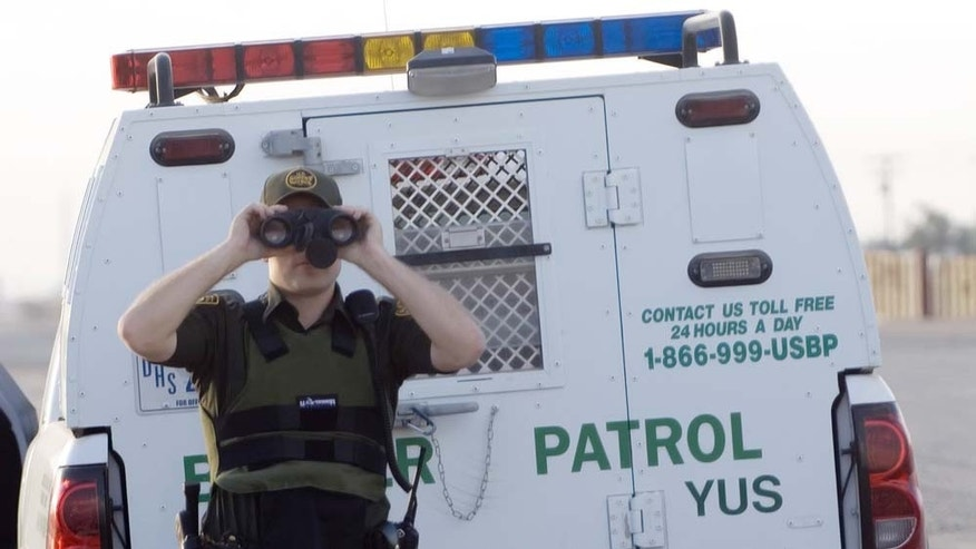 SAN LUIS, AZ - JUNE 7:  A U.S. Border Patrol agent uses binoculars to spot an illegal immigrant as he tries to climb over a 15-foot high border fence with Mexico at dawn June 7, 2006 in San Luis, Arizona. The agent, who was dragging tires behind his truck so he can spot new footprints in the sand, went to the site to see the man hurry over the fence, back into Mexico. The fence runs for six miles along the San Luis border, and is being extended 1,000 yards by Members of the Utah National Guard in a two-week training program that has become part of Presidents Bush?s Operation Jumpstart to send some 6,000 National Guard to the Border this year.  (Photo by Gary Williams/Getty Images)