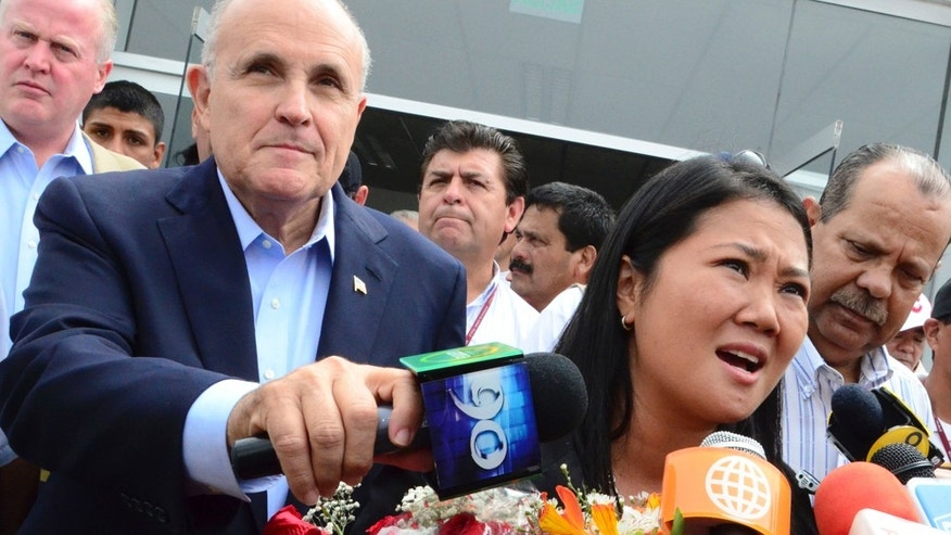 Peru's presidential candidate Keiko Fujimori, right, of the political party Fuerza 2011 and daughter of Peru's former President Alberto Fujimori, right, talks with reporters next to Rudolph Giuliani, former Mayor of New York City, left, in Trujillo, Peru, Sunday, May 15, 2011. Guiliani is in Peru invited by Keiko Fujimori, who will face Ollanta Humala in a presidential elections runoff election June 5. (AP Photo/La Industria de Trujillo)