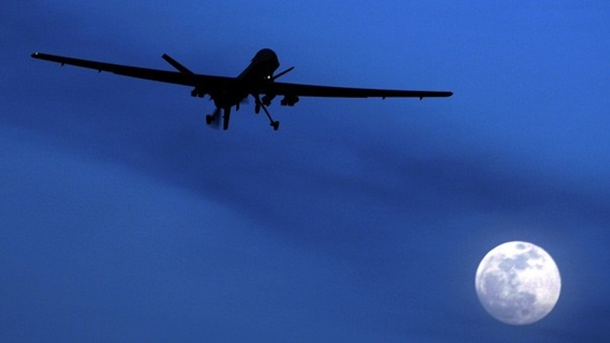 A U.S. Predator drone flies over the moon above Kandahar Air Field, Afghanistan.