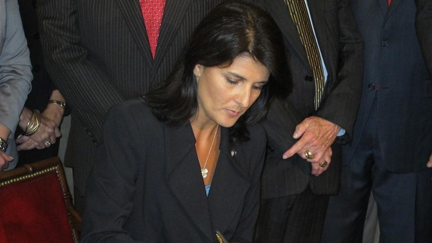 South Carolina Gov. Nikki Haley signs a bill May 18, 2011 that requires voters to present valid photo ID at the polls. The law, however, will not take effect until approved by the Justice Department (Fox News Photo)