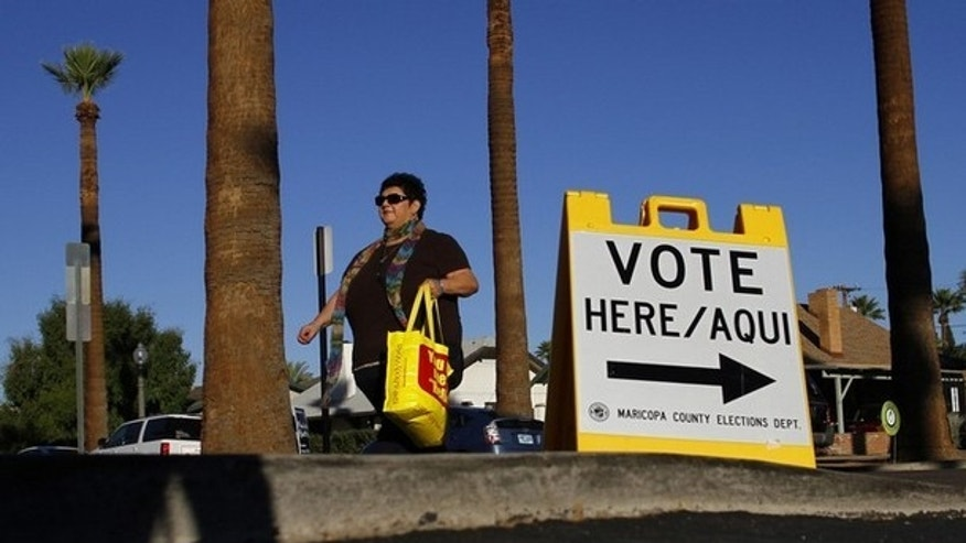 A woman walks past a sign directing voters to a polling place in the Phoenix, Ariz., Nov. 2, 2010.