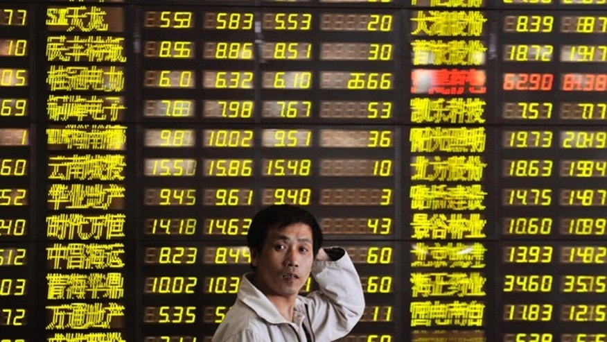 May 23, 2011: A Chinese investor reacts as he walks past an electronic board displaying falling stock prices at a brokerage house in Shenyang, Liaoning province.