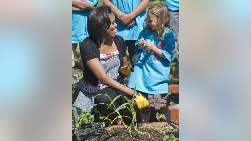 "First lady Michelle Obama tends the White House garden in Washington, Friday, June 3, 2011, with a group of children as part of the ""Let's Move!"" campaign. (AP Photo/Evan Vucci)"