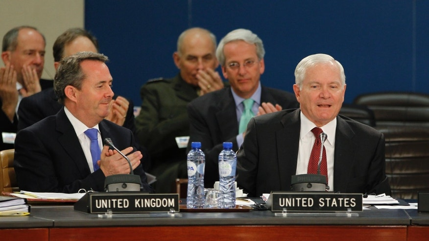 June 8: U.S. Secretary of Defense Robert Gates, right, is applauded by British Defense Secretary Liam Fox during a meeting of the North Atlantic Council at the NATO Defense Ministers Summit in Brussels. NATO's top official said Wednesday the alliance won't put troops on the ground in Libya to keep order once the civil war ends and it will be up to the United Nations to help the north African country toward its future once Qaddafi is no longer at its helm.  (AP/Pool)