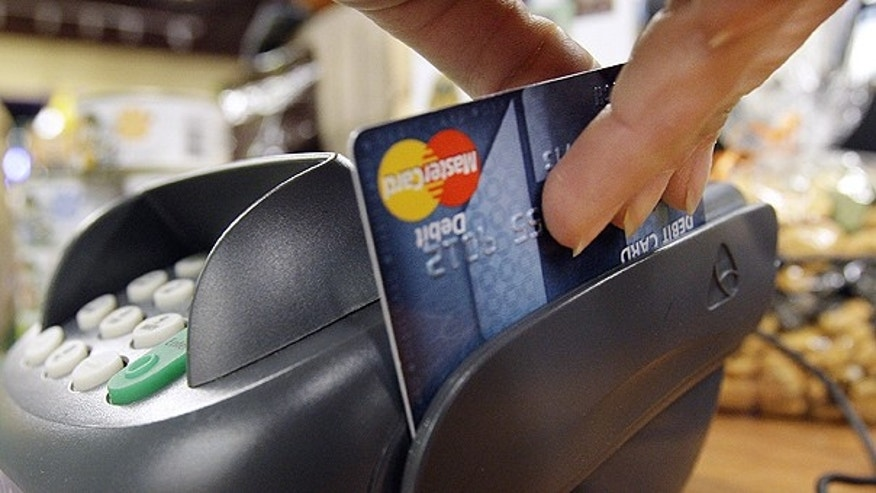 In this Nov. 2, 2009 file photo, a customer swipes a MasterCard debit card through a machine while checking-out at a shop in Seattle. Consumers are wedged in the middle of a fight between bankers and merchants as the Senate plans a showdown vote over whether to limit fees that stores pay financial institutions every time a debit card is swiped.