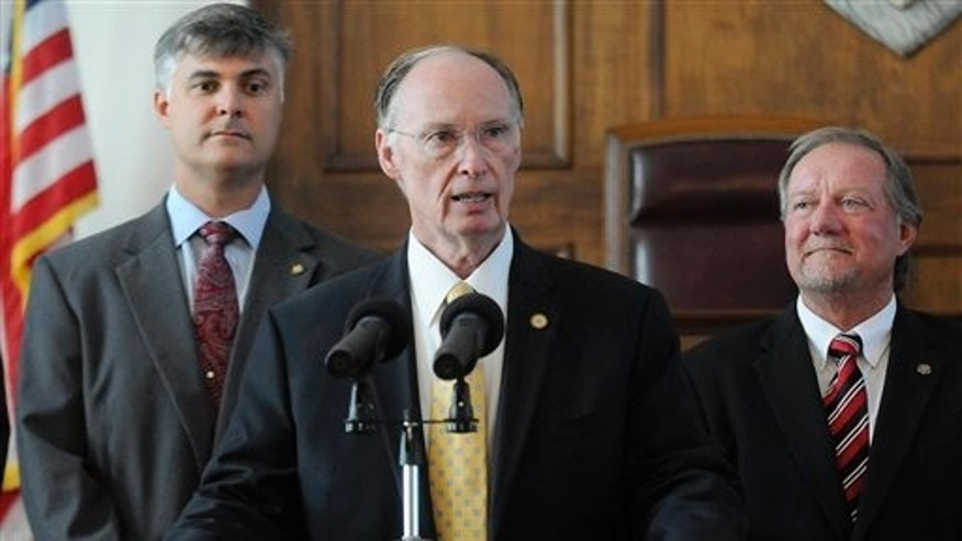 June 9: Alabama Gov. Robert Bentley is flanked by Sen. Scott Beason, R-Gardendale, left, and Micky Hammon, R-Decatur, right, as he speaks before signing into law what critics and supporters are calling the strongest bill in the nation cracking down on illegal immigration, at the state Capitol in Montgomery, Ala. The bill allows police to arrest anyone suspected of being an illegal immigrant if they're stopped for any other reason. It also requires public schools to determine students' immigration status and makes it a crime to knowingly give an illegal immigrant a ride. (AP)