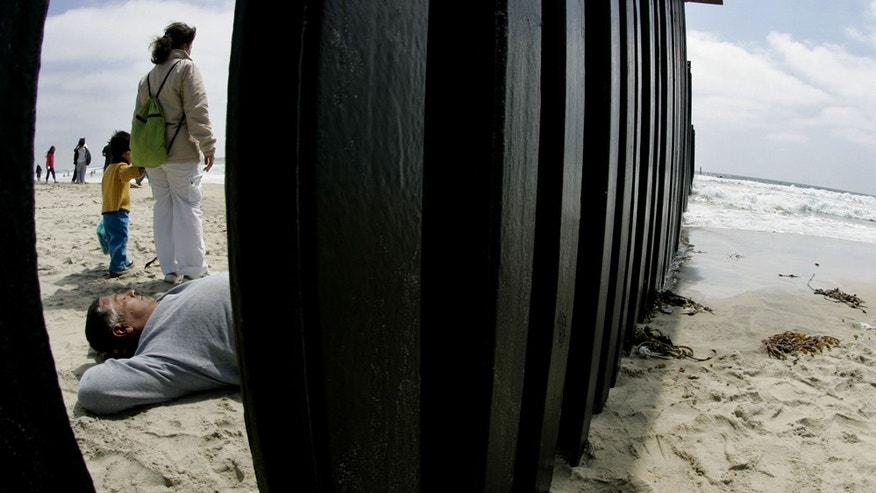 JUNE 10:  A Mexican National lays out on the beach along the U.S. and Mexico border wall June 10, 2007 in San Ysidro, California.  (Photo by Sandy Huffaker/Getty Images)