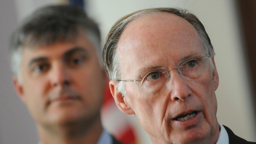 Sen. Scott Beason R-Gardendale, left, listens as Alabama Gov. Robert Bentley speaks before signing into law what critics and supporters are calling the strongest bill in the nation cracking down on illegal immigration, on Thursday June 9, 2011 at the state Capitol in Montgomery, Ala. (AP)