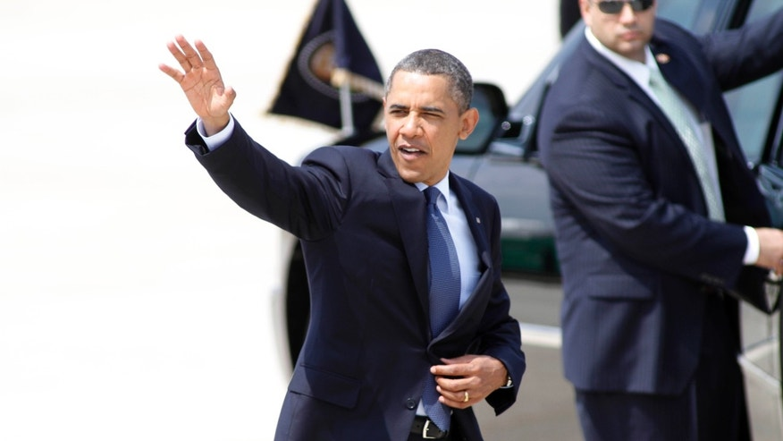 President Barack Obama waves to spectators after arriving at Raleigh Durham International Airport in Morrisville, N.C., Monday, June 13, 2011. (AP Photo/Jim R. Bounds)