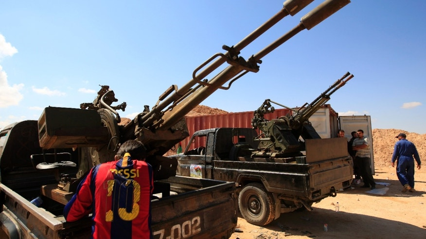 Tuesday: A Rebel fighter wearing FC Barcelona soccer player Lionel Mess T-shirt stands next to his heavy weapon, preparing for clashes with pro-Muammar al-Qaddafi forces at the front line of Dafniya, about 25 miles west of Misrata, Libya.