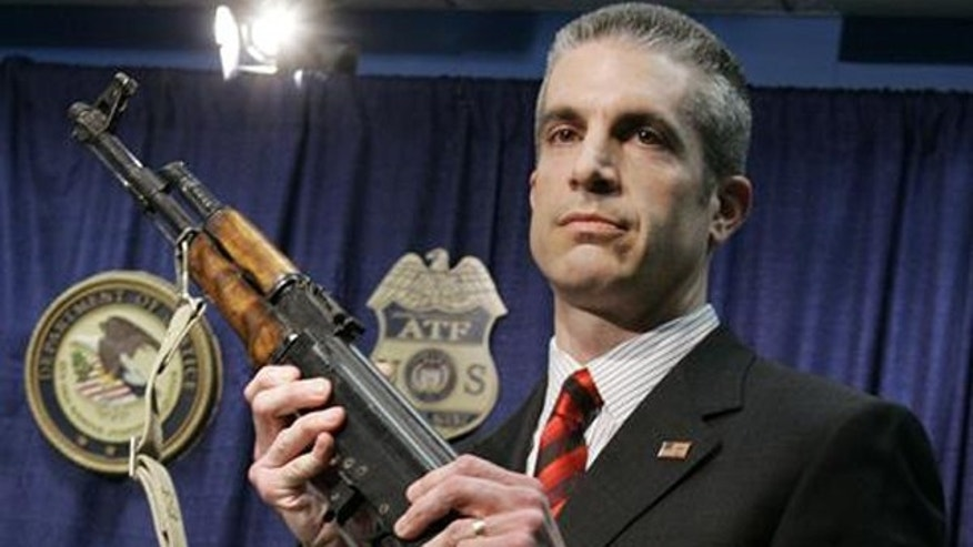 File: In this Feb. 28, 2007, photo, ATF Chicago chief Andrew Traver displays an assault weapon from a confiscated cache.