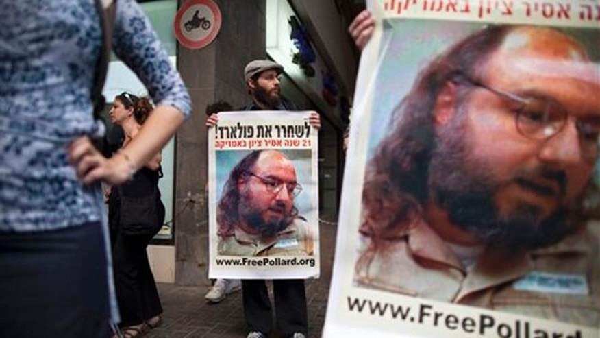 Israeli protesters hold posters demanding the release of Jonathan Pollard, a Jewish American who was jailed for life in 1987 on charges of spying on the United States, as they stand outside the U.S. embassy in Tel Aviv, Israel,  Sunday, June 19, 2011. Israelis are rallying behind convicted spy Jonathan Pollard like never before, urging the U.S. on Sunday to let the former Pentagon analyst leave prison to attend his father's funeral.