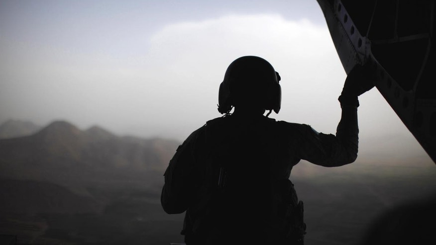 A U.S. Army crewman sits at the rear of a CH-47 Chinook helicopter over eastern Afghanistan, Monday, June 6, 2011. (AP Photo/Jason Reed, Pool)