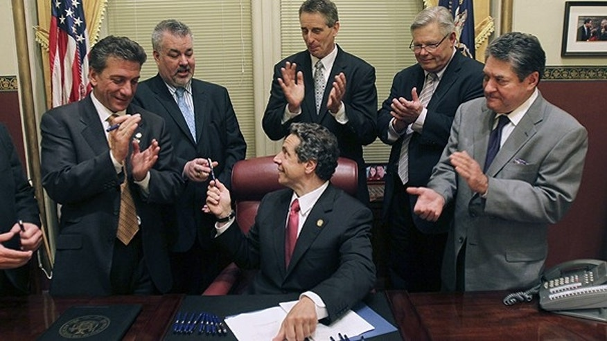 June 24: New York Gov. Andrew Cuomo, center, hands pens to legislators after signing into law a bill legalizing same-sex marriage, at the Capitol in Albany, N.Y.