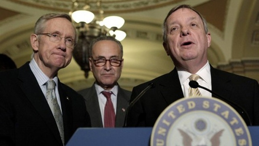 Sen. Dick Durbin, right, speaks to the media, alongside Senate  Majority Leader Harry Reid, left, and Sen. Charles Schumer on Capitol Hill in Washington June 23.