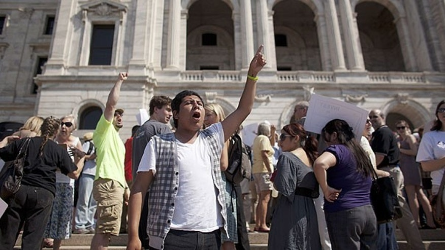 June 30: Richard Aviles of Northfield, Minn., leads the chanting of demonstrators opposed to a state shutdown on the steps of the state Capitol in St. Paul, Minn., (AP Photo/Star Tribune, Jeff Wheeler) .
