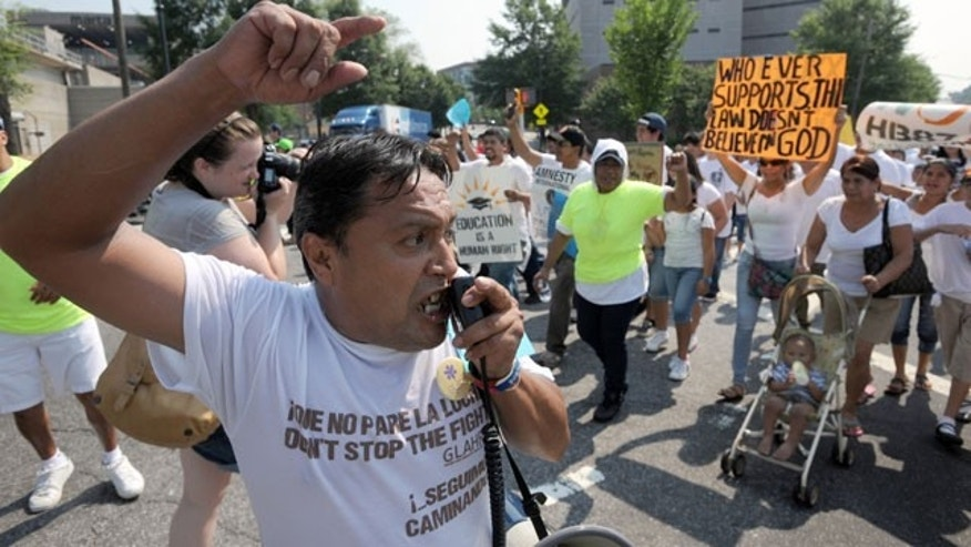 Tomas Martinez shouts slogans while leading thousands of people in a march through downtown Atlanta in protest against Georgia's strict new immigration law on Saturday, July 2, 2011 in Atlanta.