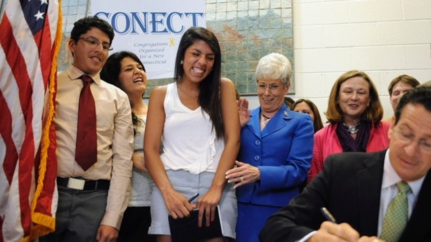 Maria Praeli, a native of Peru, third from left, reacts as Gov. Dannel P. Malloy, right, signs a ceremonial bill to expand educational access as family and Lt. Gov. Nancy Wyman, third from right, look on, in New Haven, Conn., Thursday, July 7, 2011. As an undocumented immigrant, Praeli can qualify for in-state at Connecticut's public universities under a new state law. (AP Photo/Jessica Hill)