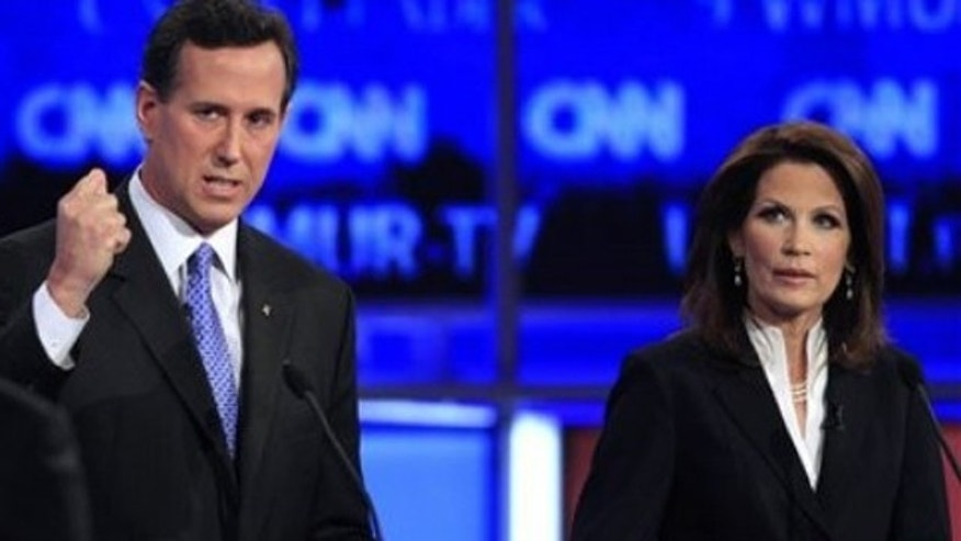 Former Pennsylvania Sen. Rick Santorum answers a question from CNN's John King, left, as Rep. Michele Bachmann, R-Minn., right, listens during the first New Hampshire Republican presidential debate at St. Anselm College in Manchester, N.H., Monday, June 13, 2011. (AP Photo/Jim Cole)