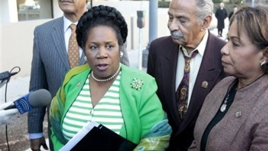 Rep. Sheila Jackson Lee, accompanied by Rep. John Conyers, center, and Rep. Barbara Lee, right, speak with reporters outside the Libyan Embassy in Washington, in this March 1, 2011 file photo.