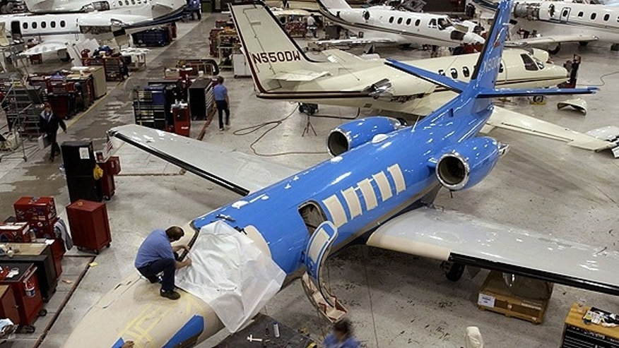 In this Nov. 4, 2004 file photo, workers service Cessna Citation business jets at Cessna's service center in Wichita, Kan.