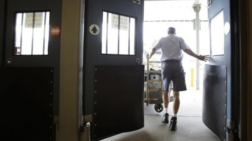 An Ohio letter carrier heads out from his branch post office with his cart full of mail to be delivered in Akron on July 16, 2010.