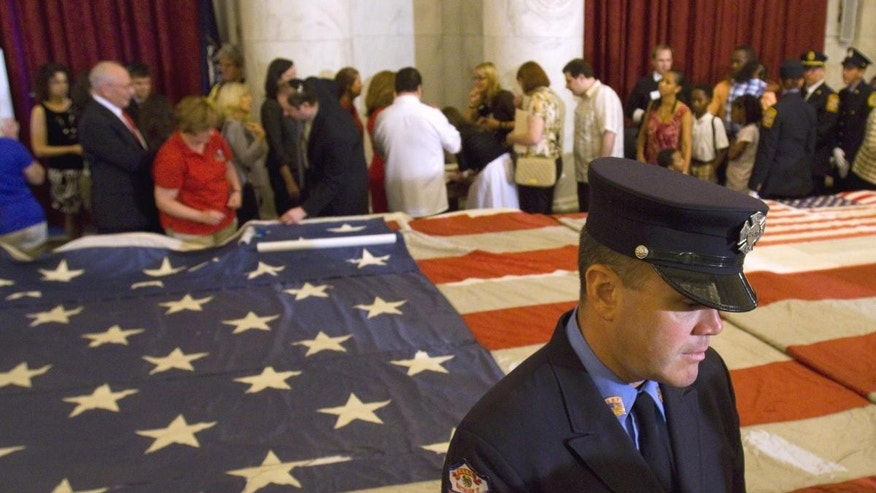 A New York City firefighter stands in front of the National 9/11 Flag