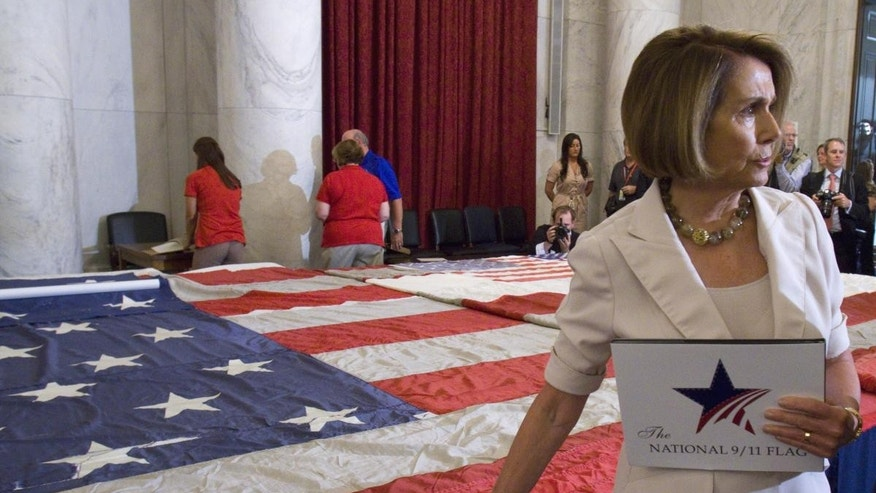 House Minority Leader Nancy Pelosi stands in front of the National 9/11 Flag
