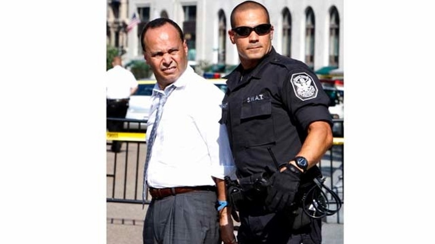 Rep. Luis Gutierrez, D-Ill., left, is arrested in front of the White House after performing an act of civil disobedience at a rally in support of the DREAM Act in Washington, Tuesday, July 26, 2011. (AP Photo/Jacquelyn Martin)