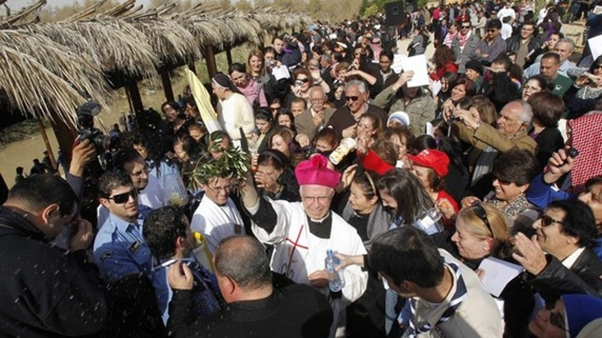 A Christian priest blesses worshippers during a mass at a baptism site on the Jordan River Jan. 14.