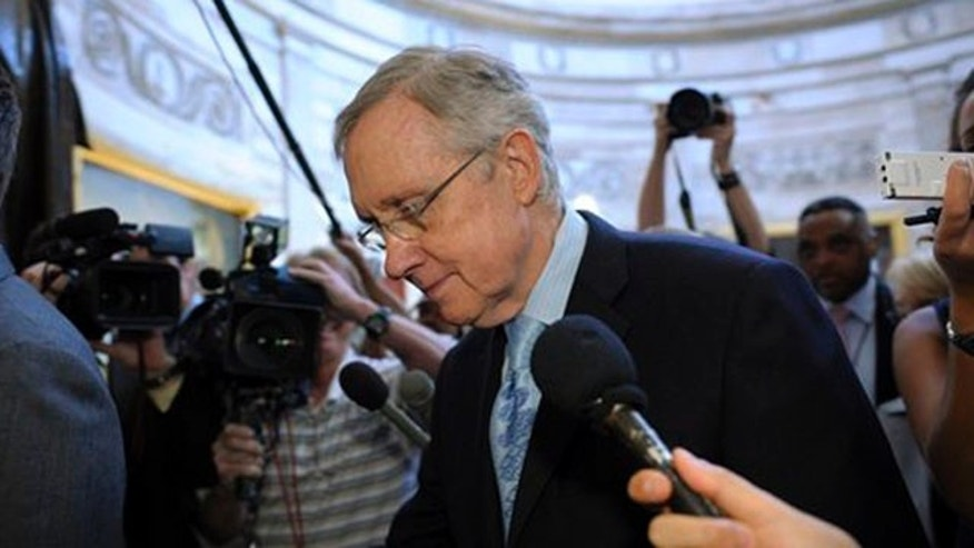 Senate Majority Leader Harry Reid is followed by reporters as he walks through the Capitol Rotunda on Capitol Hill July 31.