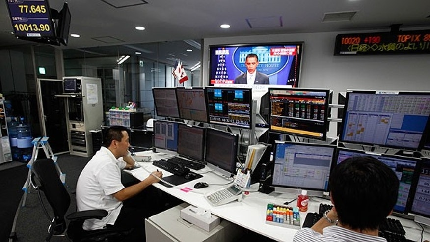 Aug. 1: Employees of a foreign exchange firm monitor screens, with a television news reports that President Obama announced U.S. debt limit deal, in Tokyo.