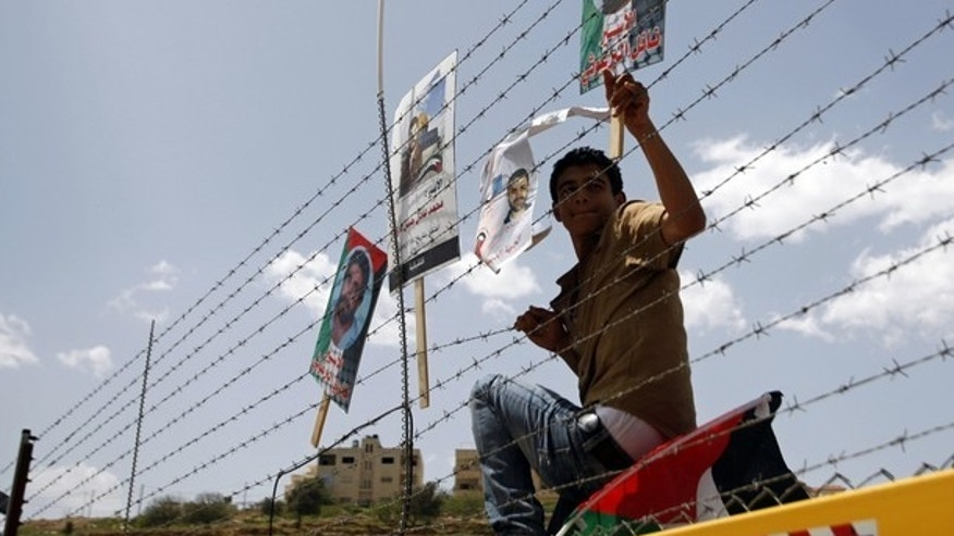 A demonstrator places a poster depicting a Palestinian prisoner, on a fence during a protest outside Ofer prison, near the West Bank city of Ramallah, April 17, 2011, calling for the release of Palestinian prisoners from Israeli jails.