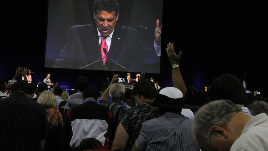 Worshippers pray with Texas Gov. Rick Perry, seen at center and on screen, at The Response, a day long prayer and fast rally, Saturday, Aug. 6, 2011, at Reliant Stadium in Houston.
