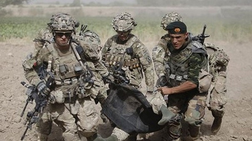 July 30: An Afghan National Army soldier along with U.S soldiers carry a wounded U.S soldier following an attack to a medevac helicopter.
