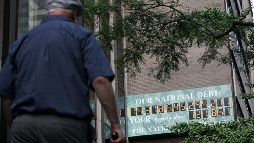 An elderly man walks past the National Debt Clock in midtown Manhattan July 13.