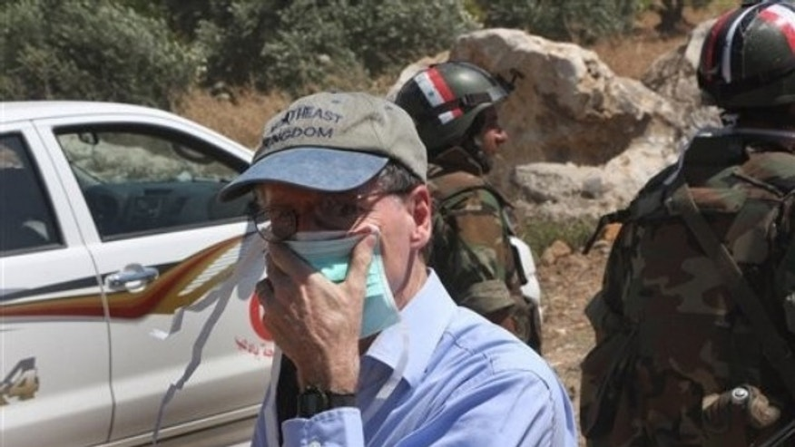 In this photo taken during a government-organized tour for foreign diplomats and the media, US ambassador in Syria Robert Ford, covers his nose from the smell of the dead bodies during his visit with other foreign diplomats to a mass grave, in Jisr el-Shughour, north of Syria, on Monday, June 20, 2011.