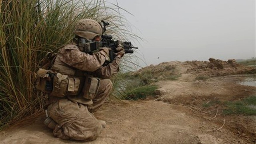 A U.S. Marine of 3rd Platoon, Kilo Company, 3/4 Marines, covers other Marines carrying boxes of U.S. Mail into their small outpost, Patrol Base 302, in Helmand province, southern Afghanistan, Friday, Aug. 26, 2011.
