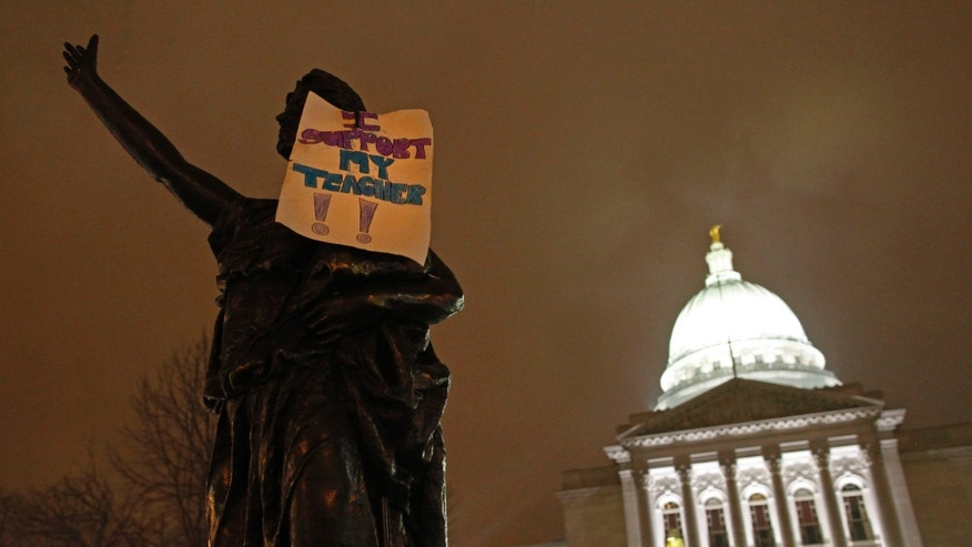 "In this Feb. 21, 2011 file photo, a sign that says ""I support my teacher"" hangs on a statue outside the state Capitol in Madison, Wis."