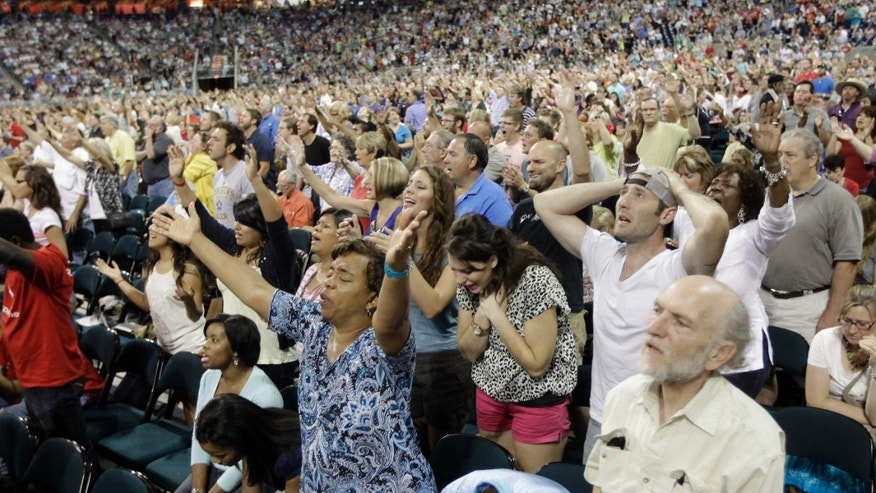 In this Aug. 6, 2011, file photo worshippers pray during The Response, a call to prayer for a nation in crisis in Houston.