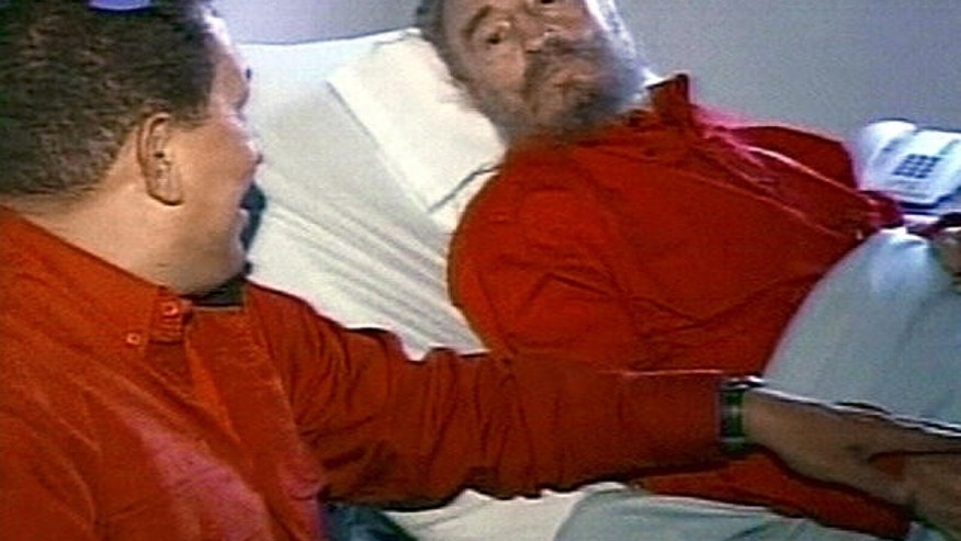 Former Cuban leader Fidel Castro, shown here in 2006 in a hospital bed, speaking with Venezuelan President Hugo Chavez.