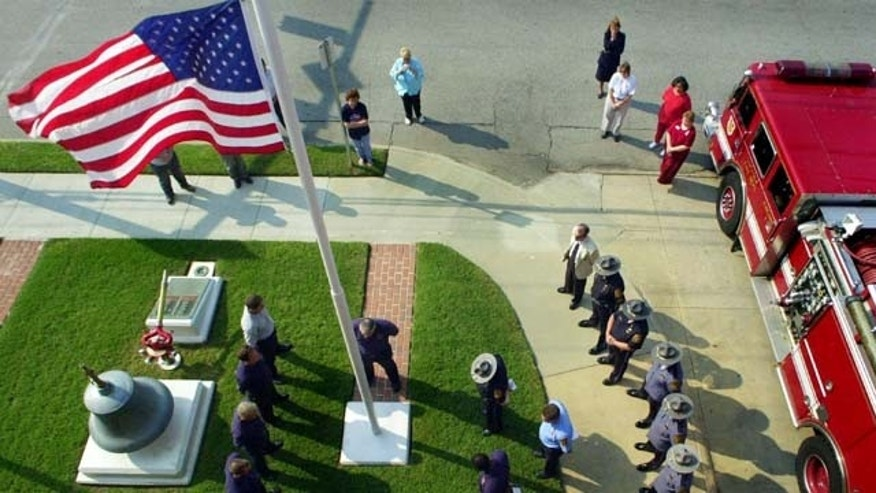SUFFOLK, VA - SEPTEMBER 11:  Members of the Suffolk fire and police departments gather at the station's flagpole for a  ceremony and a moment of silence coinciding with the collapse of the first World Trade Center tower a year ago September 11, 2002 in Suffolk, Virginia. The group returned to the flagpole almost twenty minutes later to observe another moment of silence at the time that second tower collapsed.  (Photo by Gary C. Knapp/Getty Images)